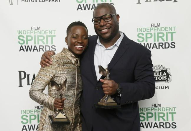 Lupita Nyong'o and director Steve McQueen pose with their awards for 12 Years a Slave backstage at the 2014 Film Independent Spirit Awards.
